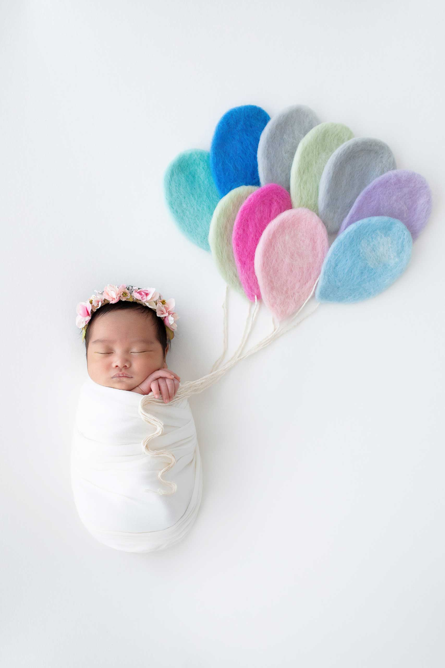 baby newborn with balloons photograph taken in Los Angeles by Ramina Magid Photography