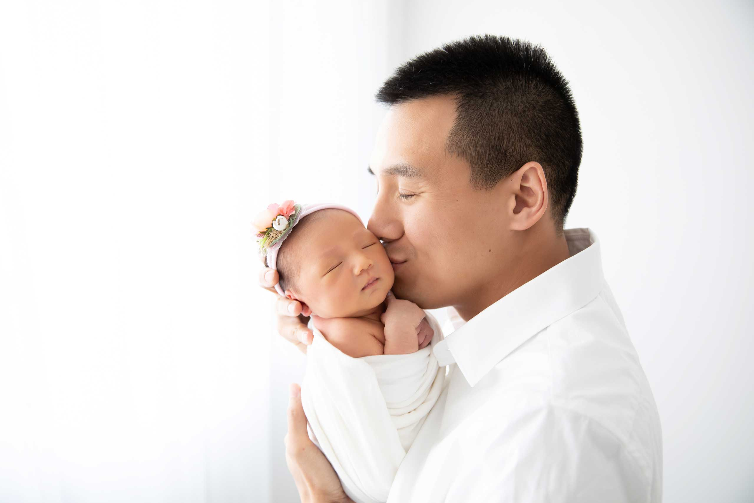 baby newborn with dad photograph taken in Los Angeles by Ramina Magid Photography